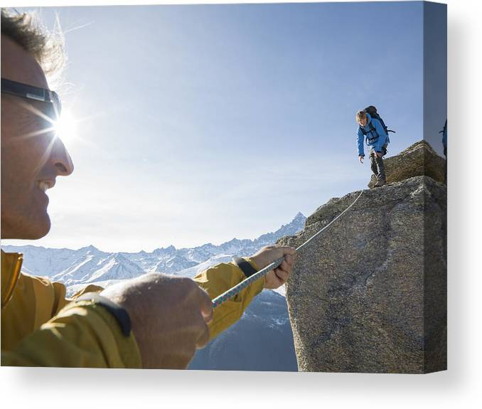Young Men Canvas Print featuring the photograph Mountaineer pulls rope tight to teammate, mtns by Ascent Xmedia