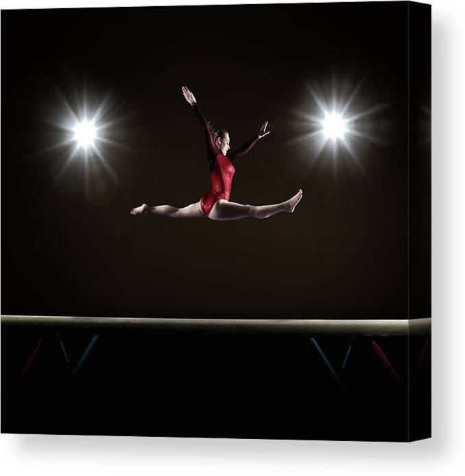 Human Arm Canvas Print featuring the photograph Female Gymnast Doing Mid Air Splits by Mike Harrington