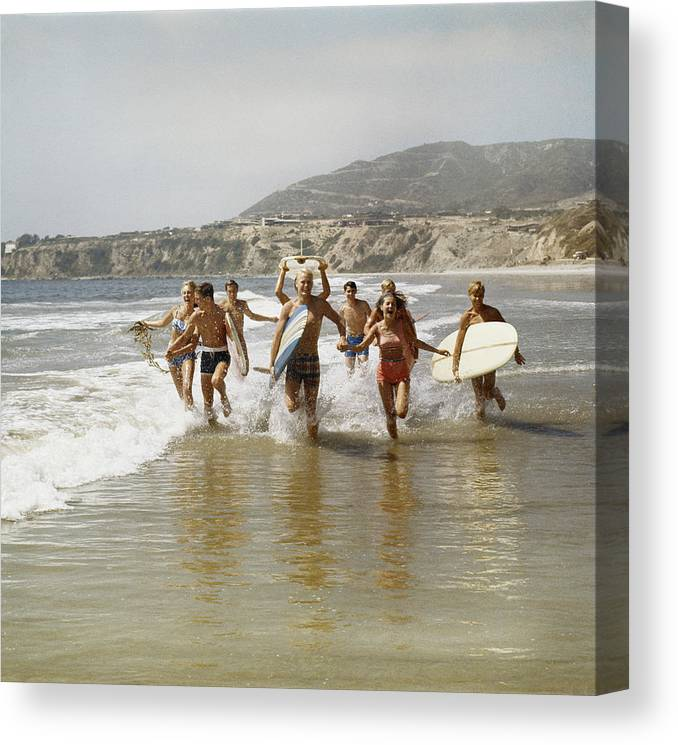 Young Men Canvas Print featuring the photograph Group Of Surfers Running In Water With by Tom Kelley Archive