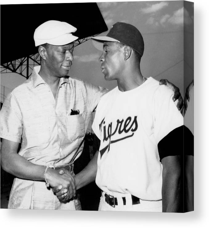 1950-1959 Canvas Print featuring the photograph Nat King Cole And Minnie Minoso by Michael Ochs Archives
