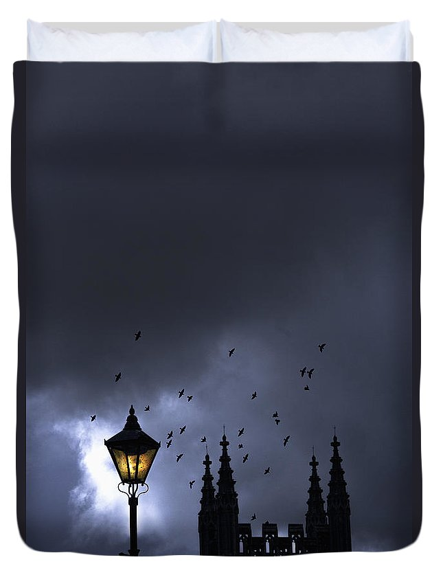 Night; Nighttime; Evening; Storm; Stormy; Clouds; Cloudy; Blue; Silhouette; Tower; Building; Church; Cathedral; Religious; Religion; Catholic; Birds; Foul; Fly; Flying; Flock; Sinister; Creepy; Scary; Eerie; Haunted; Tall; Light; Lamp; Lamppost; Lamp Post; Lit; Yellow; Blue; Gothic; Mysterious; Mystery; Crime; Horror; Thriller; Moody; Twilight Duvet Cover featuring the photograph On A Cold Dark Night by Margie Hurwich