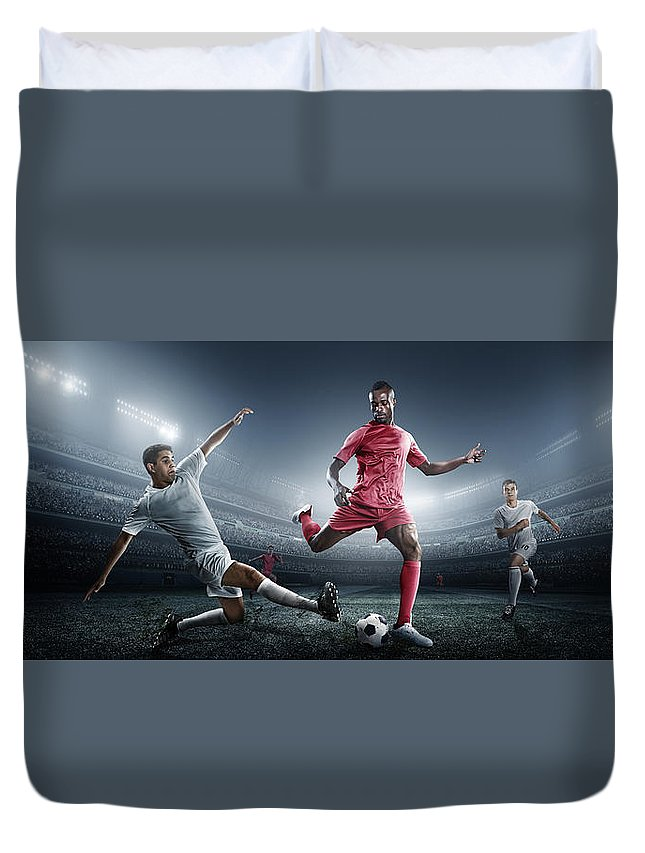 Soccer Uniform Duvet Cover featuring the photograph Soccer Player Kicking Ball In Stadium by Dmytro Aksonov