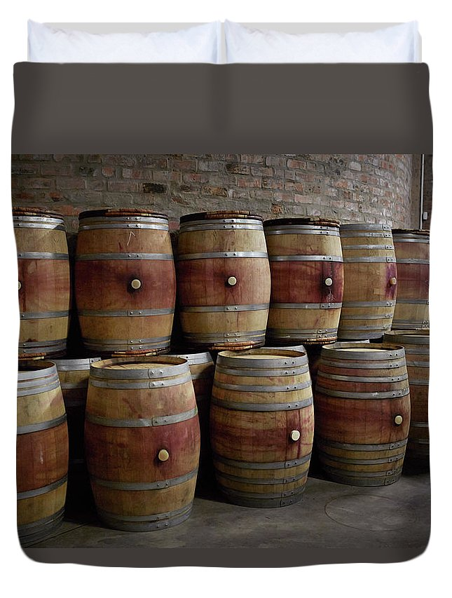 Stellenbosch Duvet Cover featuring the photograph French Wine Barrels Stacked At Winery by Klaus Vedfelt