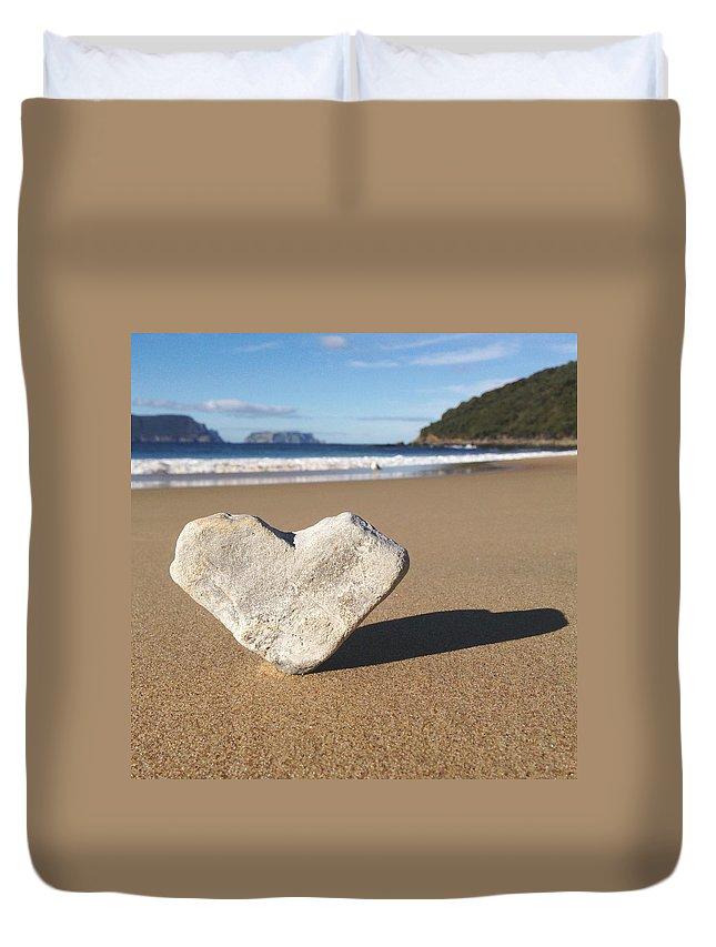 Water's Edge Duvet Cover featuring the photograph Heart Shaped Rock Sitting In Sand At by Jodie Griggs