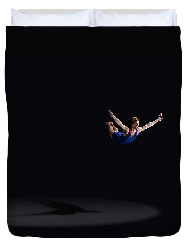 Expertise Duvet Cover featuring the photograph Male Gymnast Soaring Through The Air by Mike Harrington