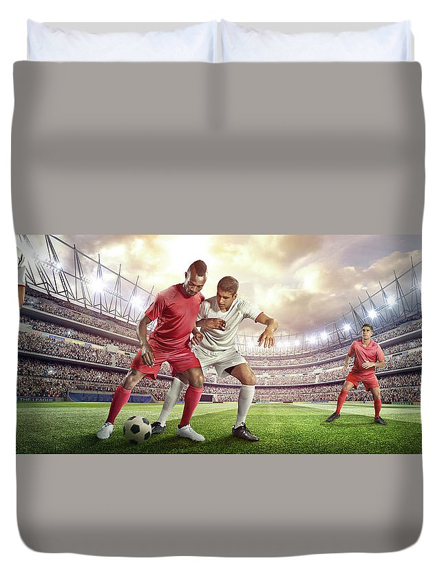 Soccer Uniform Duvet Cover featuring the photograph Soccer Player Tackling Ball In Stadium by Dmytro Aksonov