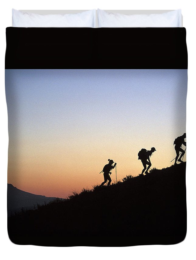 Adventure Racing Duvet Cover featuring the photograph Two Men And One Woman Run Up A Mountain by Corey Rich