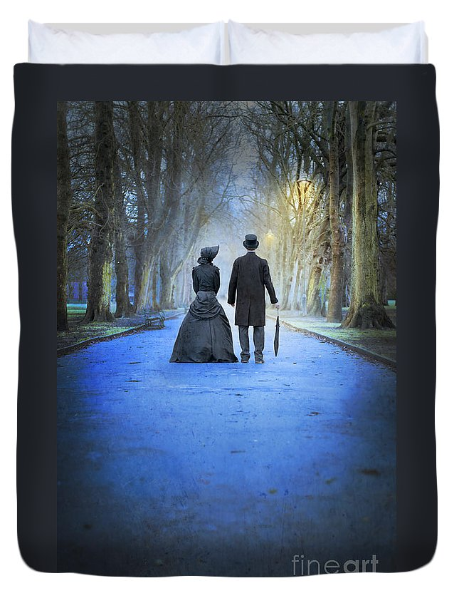 Victorian; Woman; Man; Couple; Couples; Married; Courting; Edwardian; Park; Avenue; Evening; Dusk; Twilight; Winter; Path; Bonnet; Hat; Dress; Black; Parasol. Umbrella; Tree; Trees; Copyspace; Outdoors; Outside; Old; Vintage; Period; Streetlight; Lit; Illuminated; Gas Lamp; Light; Glow; Glows; Glowing; Dawn; Street Light; Rustic; Period; Scene; Lamp Light; Antique; Street Lamp; Lantern; Lamp; Streetlamp; Lamp Post; Lamppost; Street; Stand; Standing; Silhouette; Silhouetted; 19th Century; 18th Century Duvet Cover featuring the photograph Victorian Couple In The Park At Dusk by Lee Avison