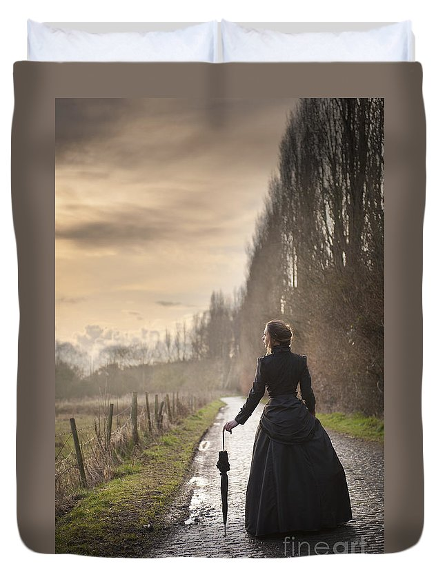Victorian Duvet Cover featuring the photograph Victorian Woman Walking On A Cobbled Avenue At Sunset by Lee Avison