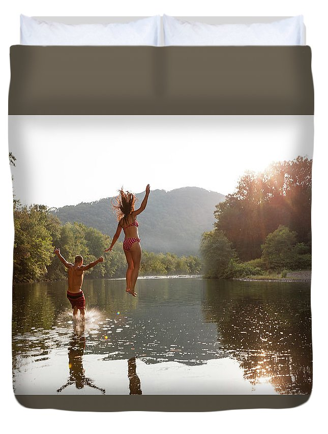Young Men Duvet Cover featuring the photograph Young Couple Jumping Into River by Zave Smith