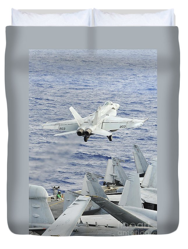 Uss George Washington Duvet Cover featuring the photograph An Fa-18e Super Hornet Launches by Stocktrek Images