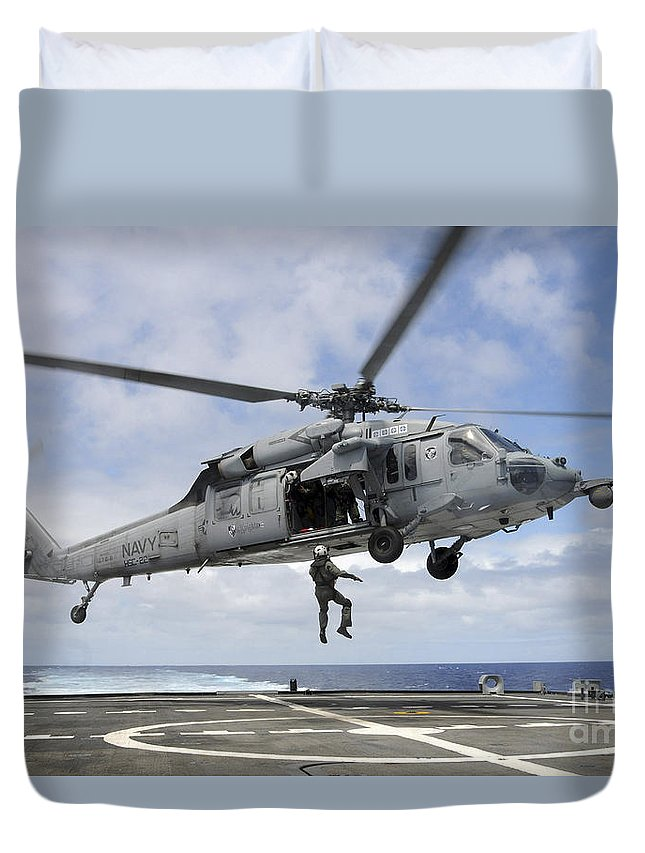 Rimpac Duvet Cover featuring the photograph A Naval Aircrewman Is Hoisted Into An by Stocktrek Images