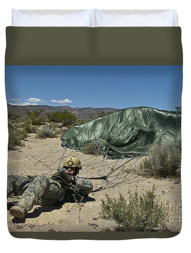Parachuting Duvet Cover featuring the photograph A Paratrooper Recovers After Landing by Stocktrek Images