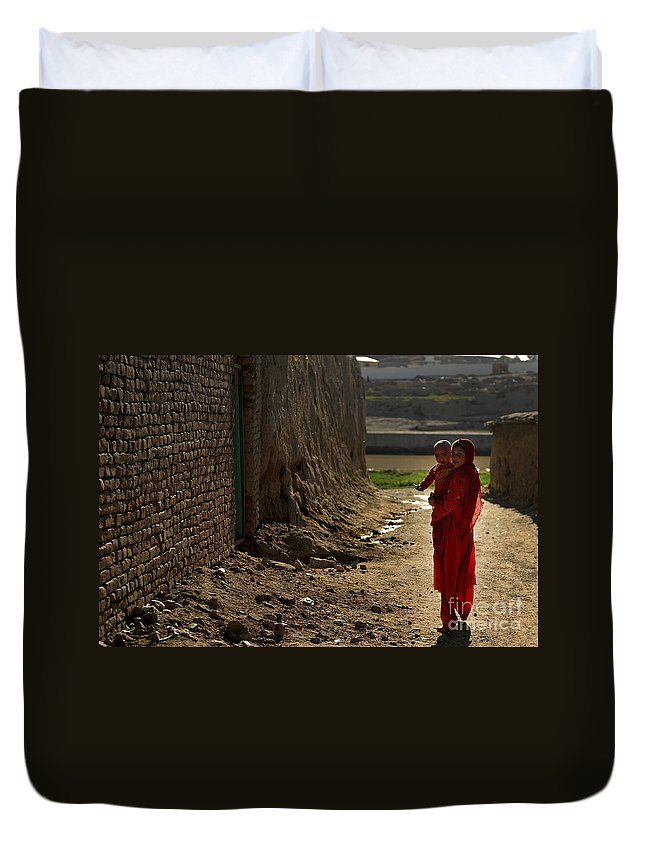 Qalat Duvet Cover featuring the photograph An Afghan Girl Carries Her Little by Stocktrek Images