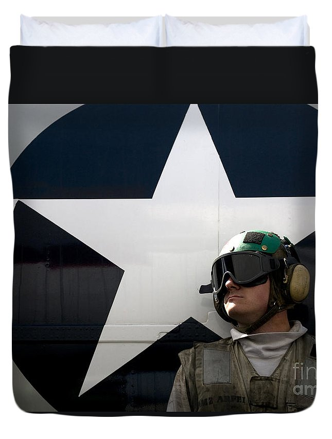 Uss Carl Vinson Duvet Cover featuring the photograph An Airman Stands In Front Of A C-2a by Stocktrek Images