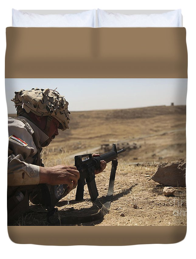 Guzlani Warrior Training Center Duvet Cover featuring the photograph An Iraqi Army Soldier Prepares To Fire by Stocktrek Images