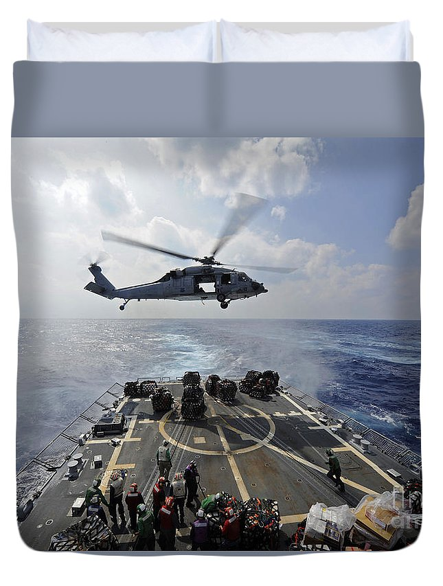 Dry Cargo Ships Duvet Cover featuring the photograph An Mh-60r Sea Hawk Transfers Supplies by Stocktrek Images
