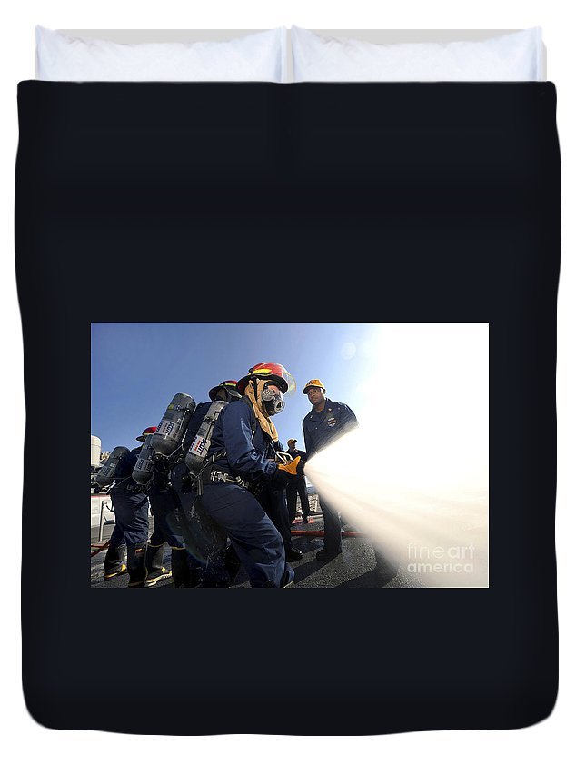 Fire Hose Duvet Cover featuring the photograph Damage Controlmen Conduct Fire Hose by Stocktrek Images