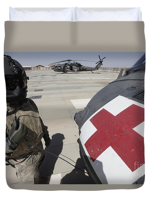 Uh-60 Blackhawk Duvet Cover featuring the photograph U.s. Army Crew Chief Inspects by Stocktrek Images