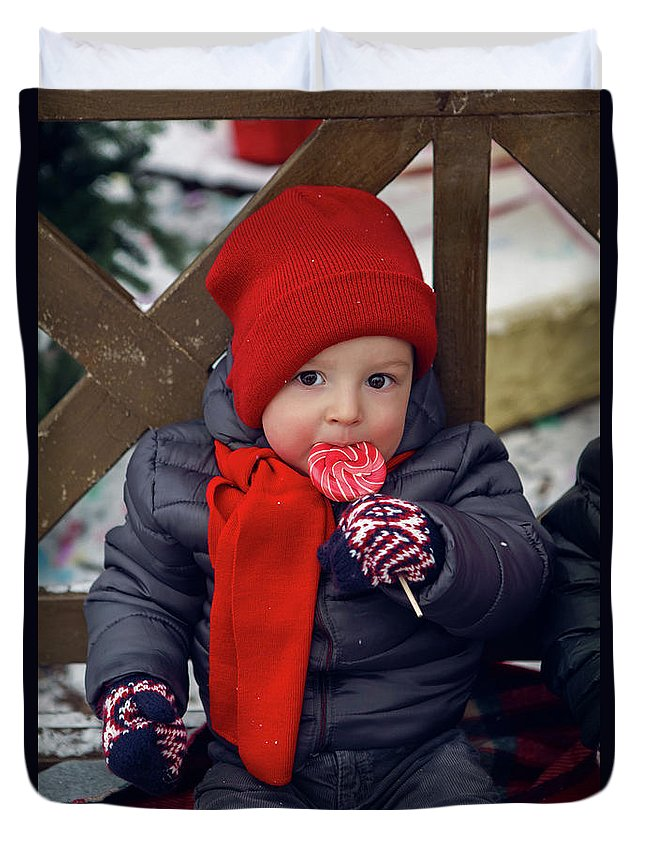 Baby Duvet Cover featuring the photograph Baby In Red Hat Sits On A Bench In The Street With Candy by Elena Saulich
