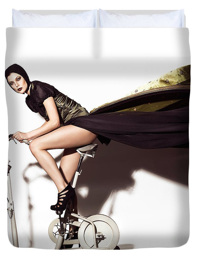 Fashion Duvet Cover featuring the photograph Young Woman In Long Dress On Exercise Bike by Oleksiy Maksymenko
