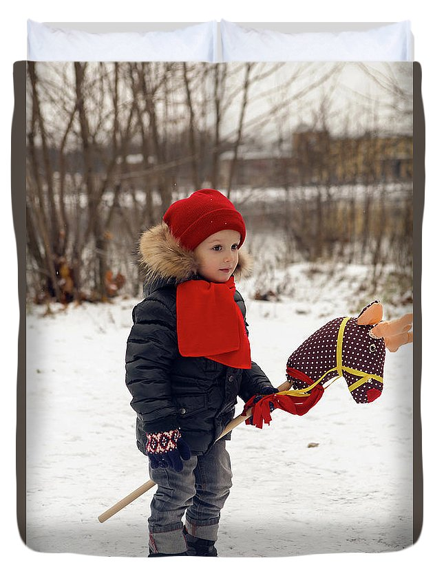 Toy Duvet Cover featuring the photograph Boy On A Toy Horse Is Standing On The Street In Winter by Elena Saulich
