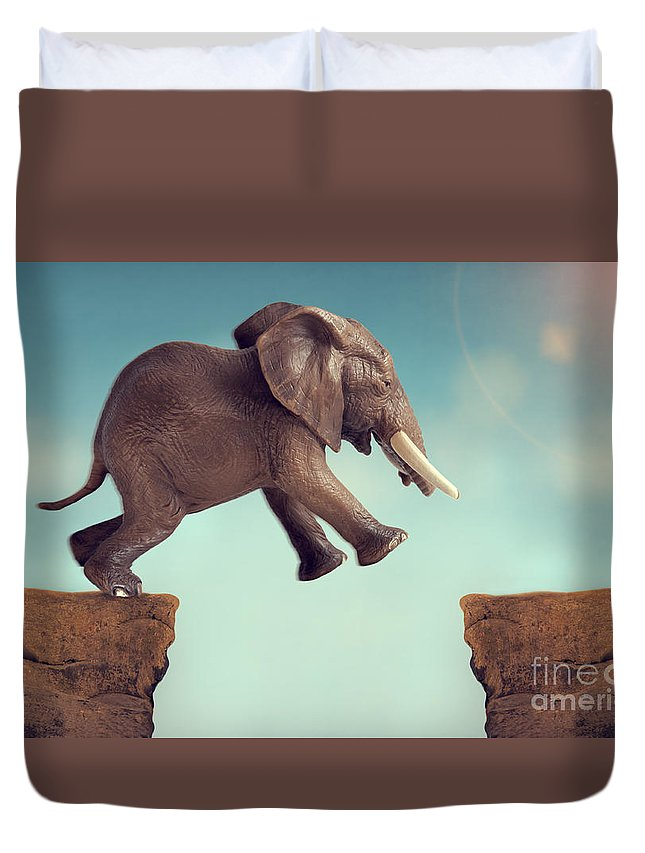 Leap Of Faith Duvet Cover featuring the photograph Leap Of Faith Concept Elephant Jumping Across A Crevasse by Lee Avison
