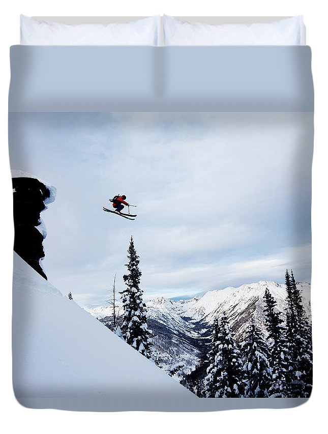 Skiing Duvet Cover featuring the photograph A Athletic Skier Jumping Off A Cliff In by Patrick Orton