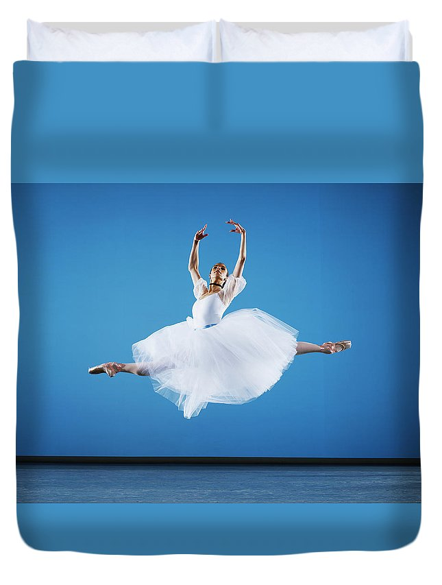 Ballet Dancer Duvet Cover featuring the photograph Ballerina Leaping On Stage, Arms Raised by Thomas Barwick
