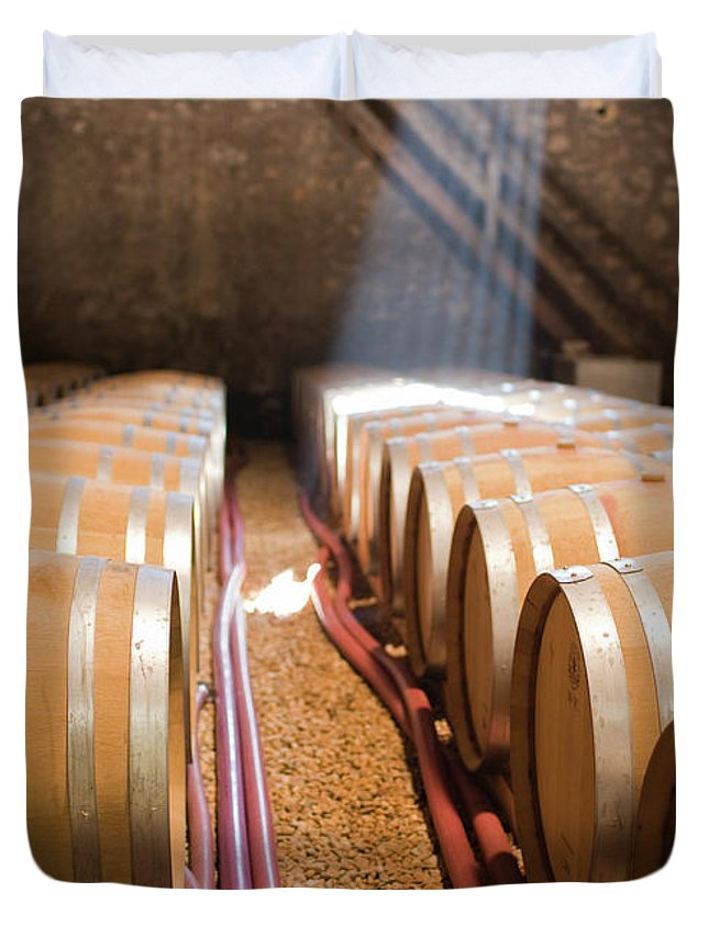 Alcohol Duvet Cover featuring the photograph Barrels In Wine Cellar by Johner Images