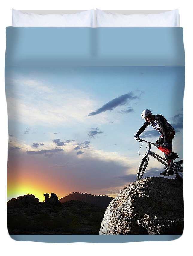 Sports Helmet Duvet Cover featuring the photograph Bike Rider Balancing On Rock Boulder by Thomas Northcut