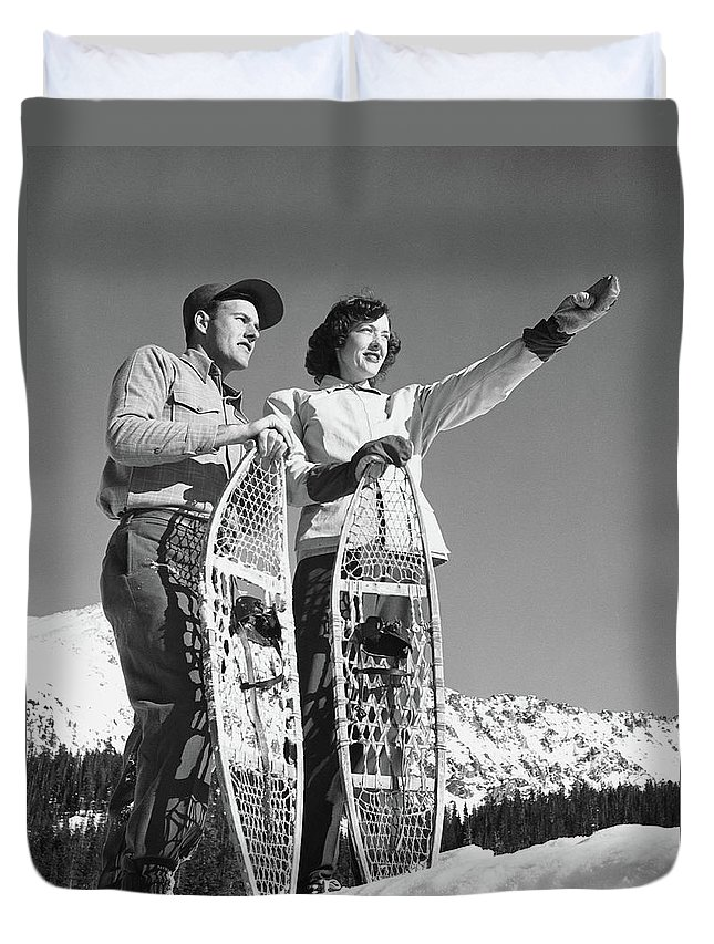Heterosexual Couple Duvet Cover featuring the photograph Couple Holding Snowshoes, Woman Pointing by Stockbyte