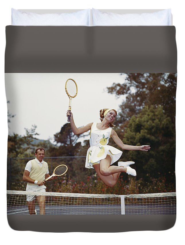Heterosexual Couple Duvet Cover featuring the photograph Couple On Tennis Court, Woman Jumping by Tom Kelley Archive