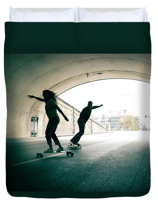 Mature Adult Duvet Cover featuring the photograph Couple Skateboarding Through Tunnel by Ian Logan
