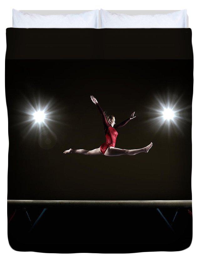 Human Arm Duvet Cover featuring the photograph Female Gymnast Doing Mid Air Splits by Mike Harrington