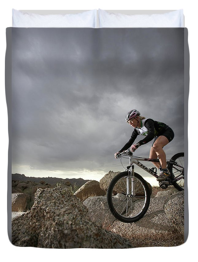Sports Helmet Duvet Cover featuring the photograph Female Rider Mountain Biking Between by Thomas Northcut