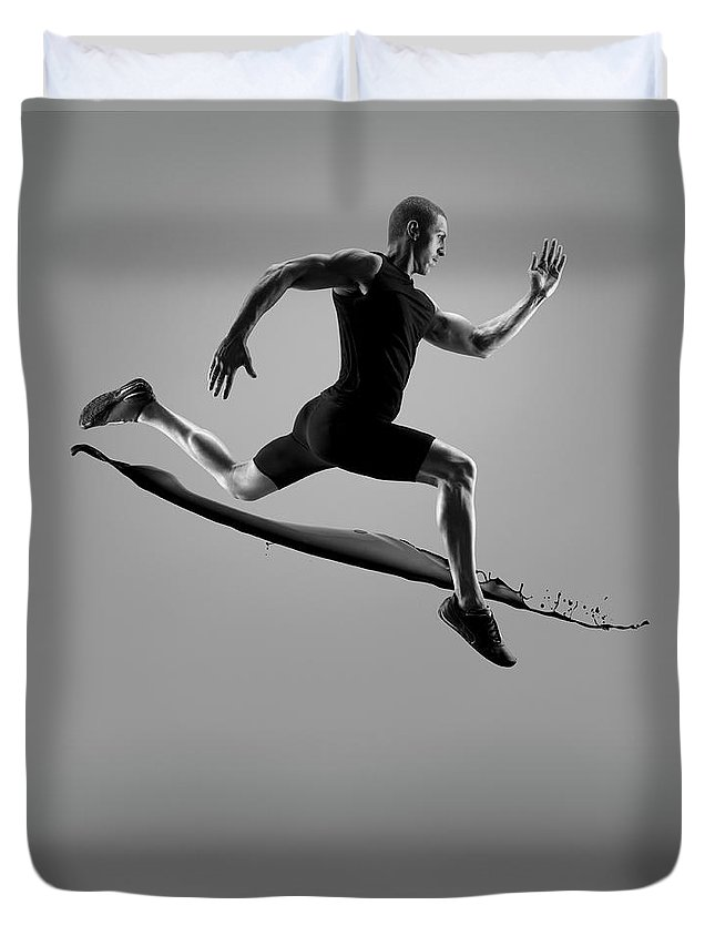 People Duvet Cover featuring the photograph Male Athlete Running Above Liquid Splash by Jonathan Knowles