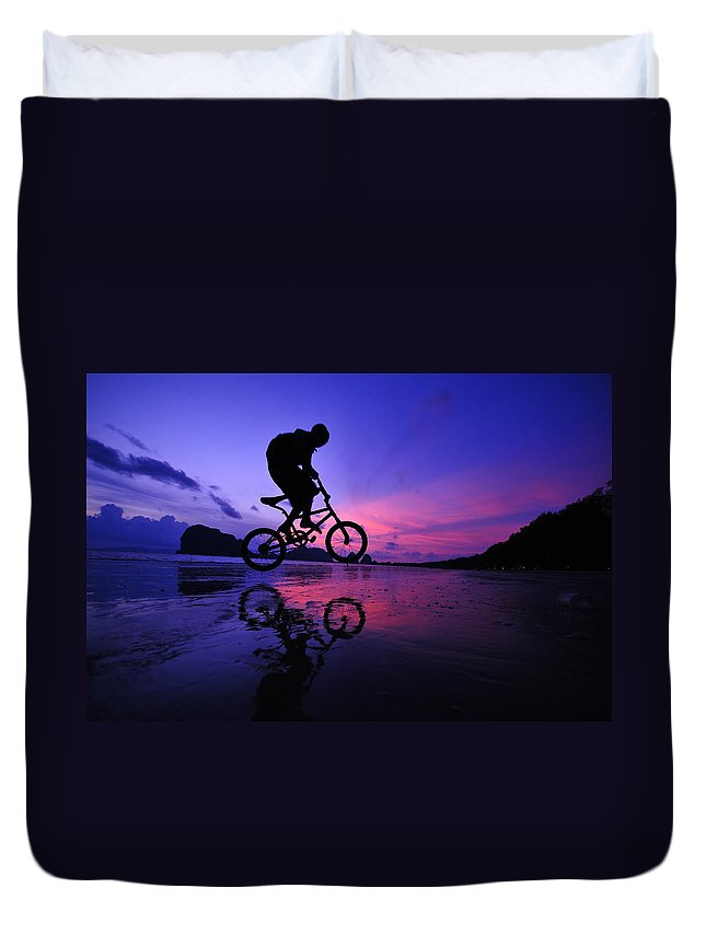 The Twilight Series Duvet Cover featuring the photograph Silhouette Of A Mountain Biker On Beach by Primeimages