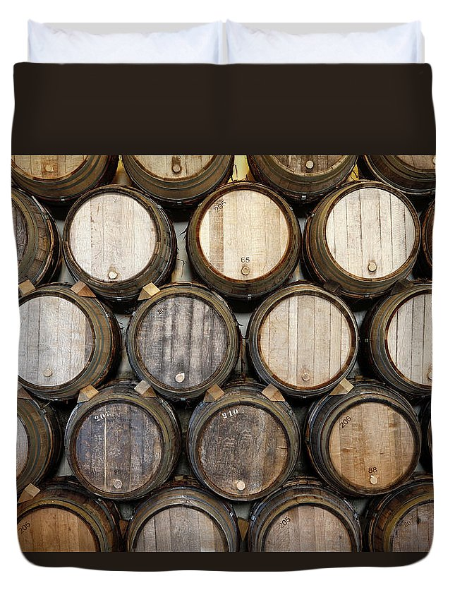 Alcohol Duvet Cover featuring the photograph Stacked Oak Barrels In A Winery by Marc Volk