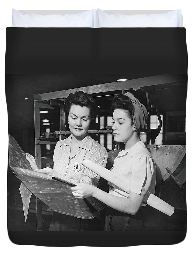 Plan Duvet Cover featuring the photograph Two Women In Workshop Looking At by George Marks