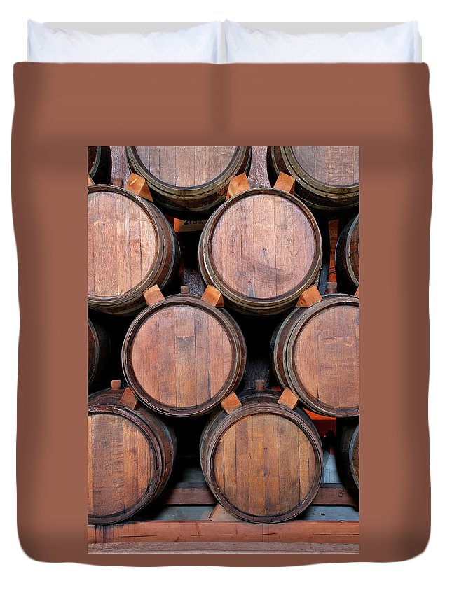 Fermenting Duvet Cover featuring the photograph Wine Barrels Stacked Inside Winery by Yinyang