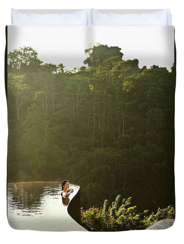 Tropical Rainforest Duvet Cover featuring the photograph Woman In Infinity Pool At Sunrise. Bali by Matthew Wakem