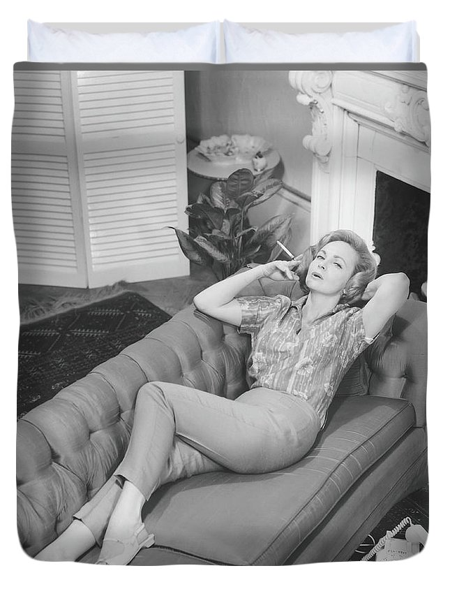 Smoking Duvet Cover featuring the photograph Woman Relaxing On Sofa, B&w, Elevated by George Marks