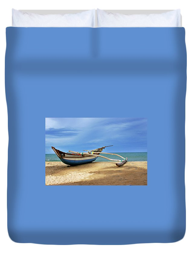 Tranquility Duvet Cover featuring the photograph Wooden Catamaran By The Sea Shore by Juavenita Alphonsus