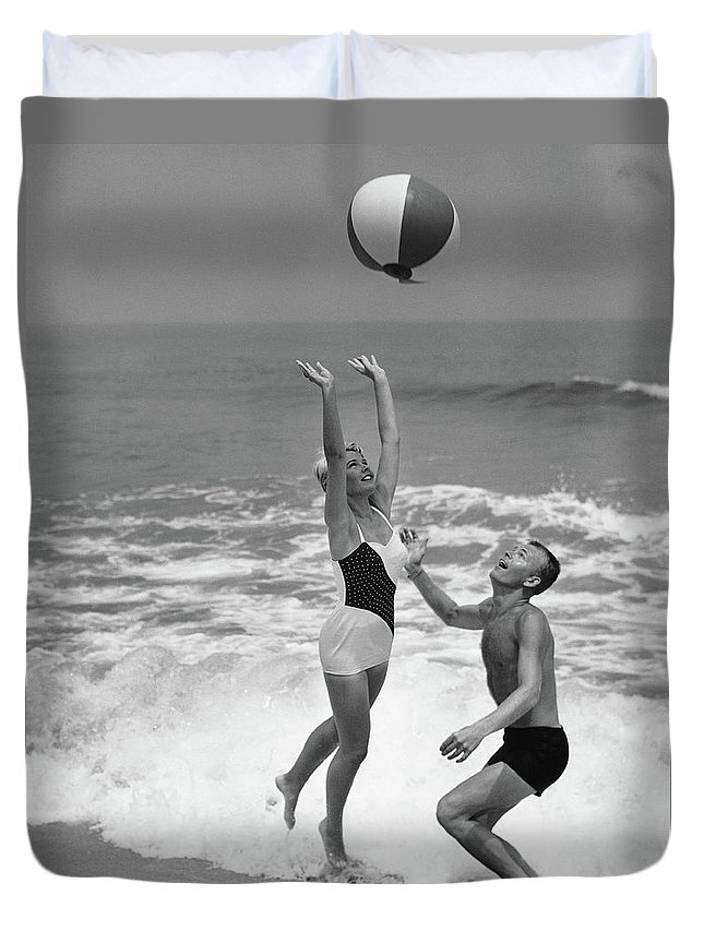 Young Men Duvet Cover featuring the photograph Young Couple Playing With Beach Ball At by Stockbyte