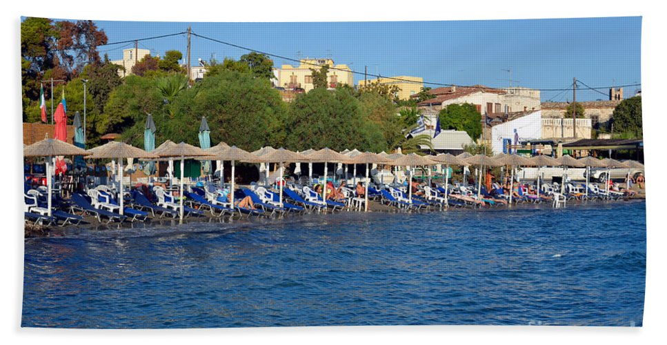 Aegina; Egina; Town; City; Port; Harbor; Sea; People; Tourists; Beach; Swim; Swimming; Sunbathing; Suntanning; Suntan; Tanning; Relaxing; Relaxation; Umbrellas; Parasols; Sunshades; Sun Beds; Sea Beds; Greece; Hellas; Argosaronic; Saronic; Gulf; Greek; Hellenic; Europe; European; Island; Islands; Holidays; Vacation; Travel; Trip; Voyage; Journey; Tourism; Touristic; Summer; Summertime Bath Sheet featuring the photograph Beach In Aegina Town by George Atsametakis