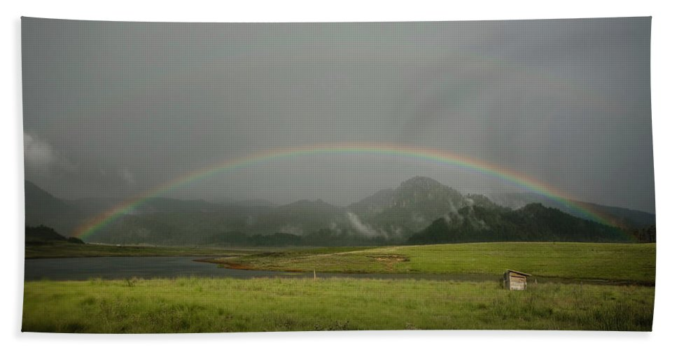 Color Image Hand Towel featuring the photograph A Rainbow Over A Valley With A Small by Marcos Ferro