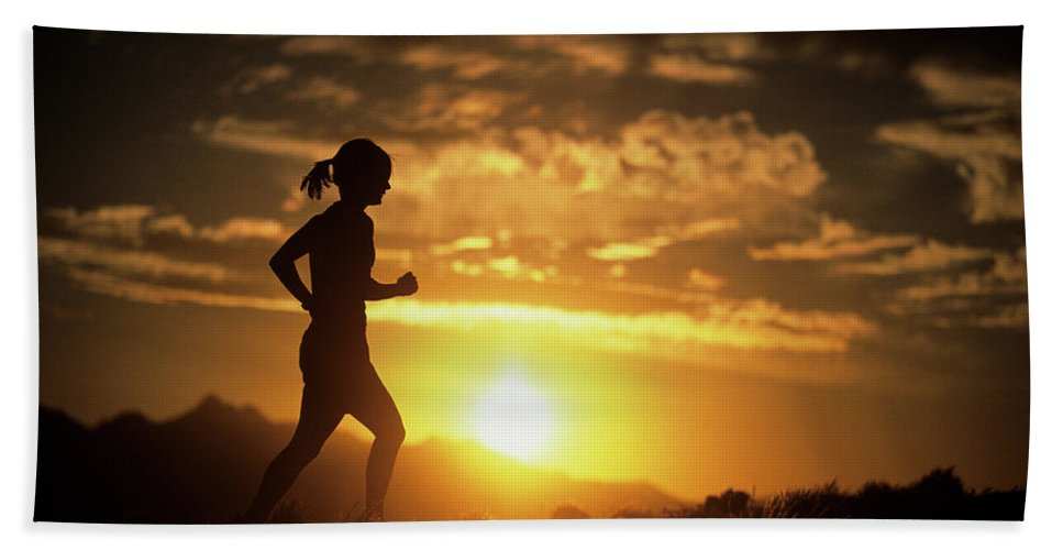 Color Image Hand Towel featuring the photograph A Woman Jogs Under Sunset by Christian Pondella