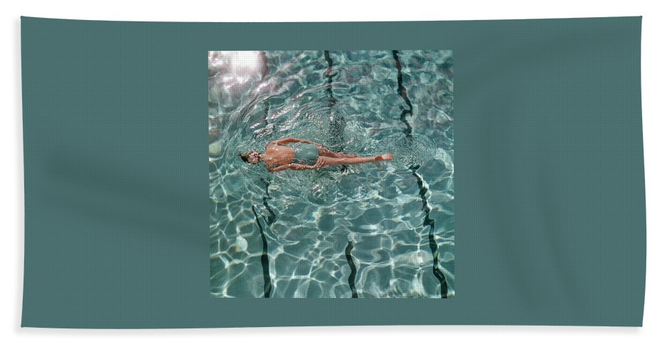 Water Bath Towel featuring the photograph A Woman Swimming In A Pool by Fred Lyon