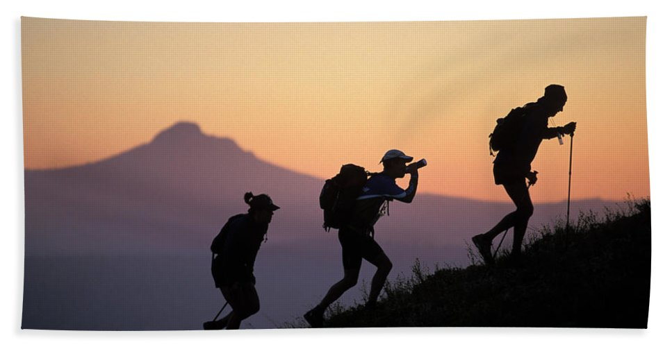 Action Hand Towel featuring the photograph Adventure Racing Team Hiking At Sunset by Corey Rich